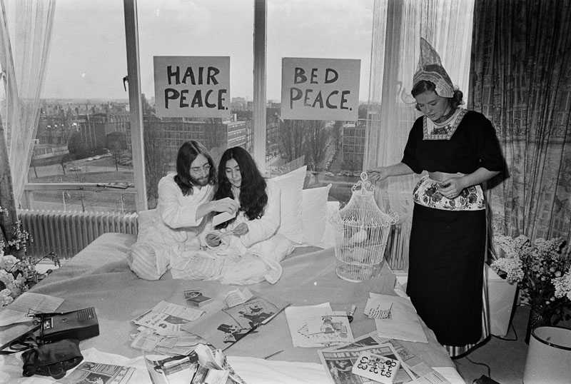Dutch lady wearing the traditional costume of Volendam offers a dove of peace to Yoko & John : Amsterdam Hilton Hotel 1969 ( Photo: Ruud Hoff)