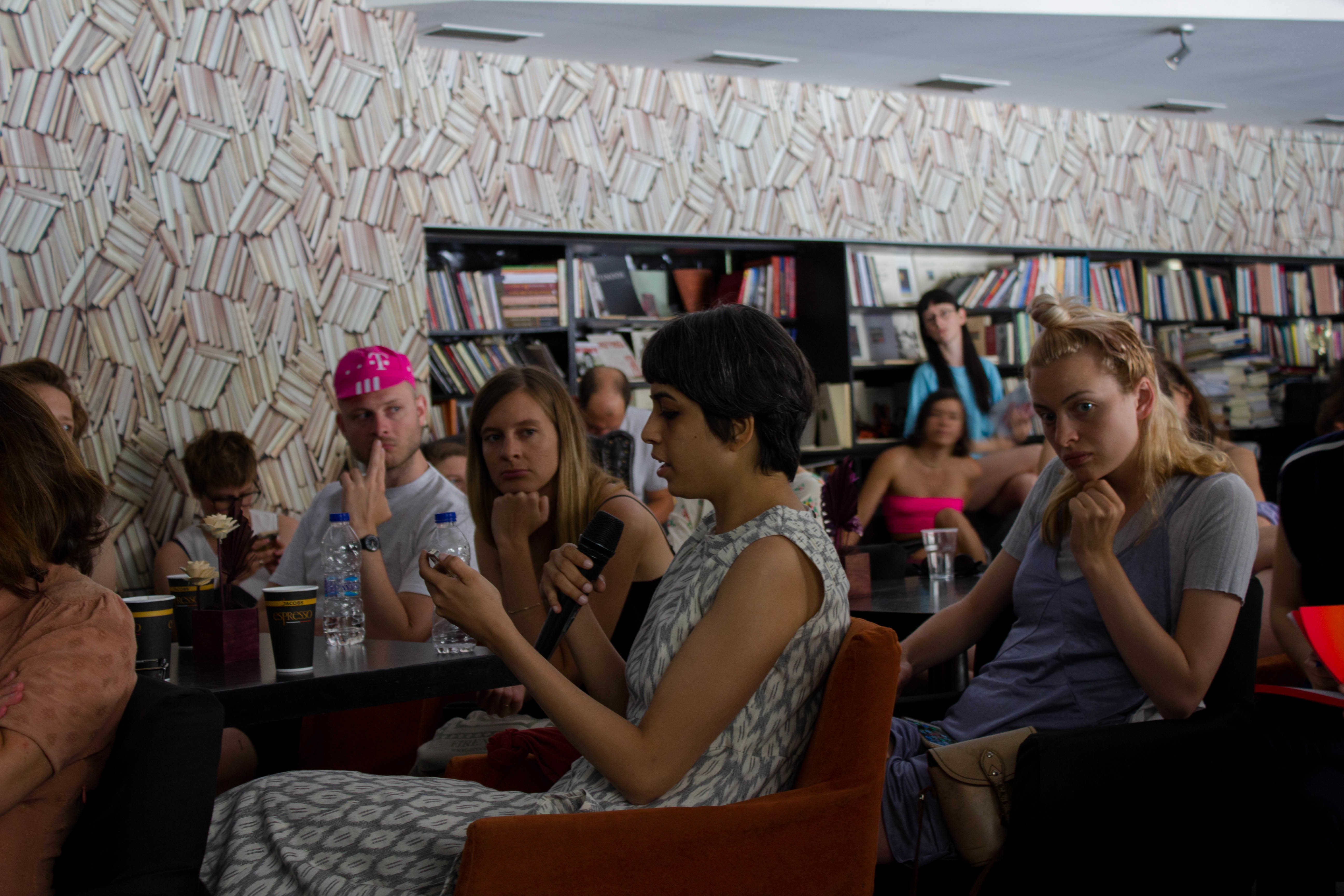 COOP SUMMIT 2018. Final presentation by the 'Proximity Aesthetics' study group at the Polis Art Cafe in Athens on June 2. In the picture: Vinita Gatne reading from the Proximity Aesthetics website on her phone. Photo: Silvia Ulloa for DAI Roaming Academy.